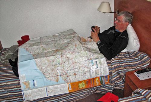 Mann im Bett mit einer Landkarte auf den Knien und einem Navi in der Hand