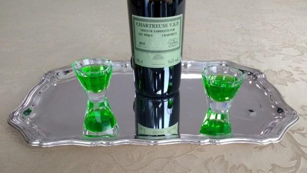 Flasche Liqueur Chartreuse mit zwei gefüllten Gläsern auf einem Silbertablett