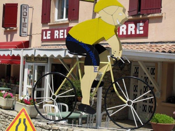 Pappschild con einem Radrennfahrer bei der Tour de France mit einem Hotel Cafe im Hintergrund
