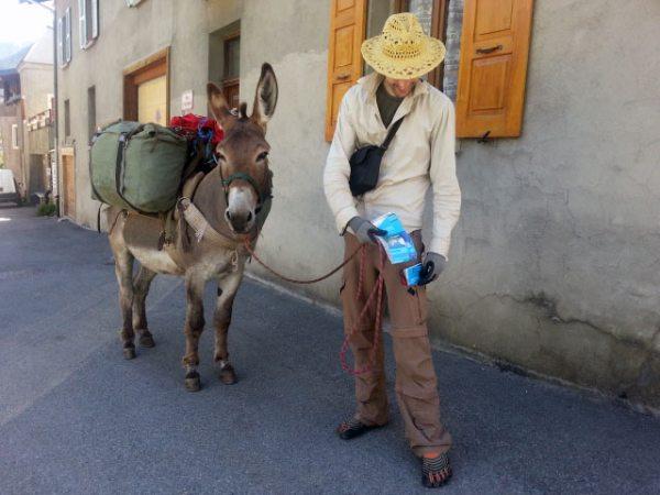 Wanderer mit einem bepackten Esel in einem französischen Gebirgsdorf bei einer Motorradtour in die Chartreuse