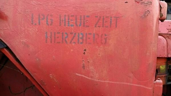 Teilansicht eines roten DDR-Traktors mit der Aufschrift LPG Neue Zeit Herzberg, gesehen bei einer Lausitztour mit dem Motorrad