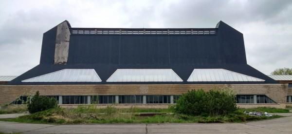 Ehemalige Hutfabrik Luckenwalde Frontansicht mit einem lang gestreckten Gebäude mit hohem schwarzen Aufbau, besucht bei einer Motorradtour zu Architektur und Musik in Brandenburg