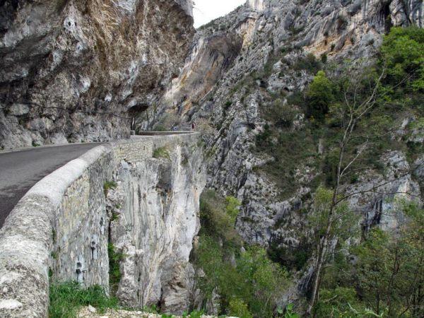Felsenstrasse mit steil abstürzenden Felswänden und Bäumen, die sich in den Felswänden festkrallen, bei einer Motorradtour durch den winterlichen Vercors