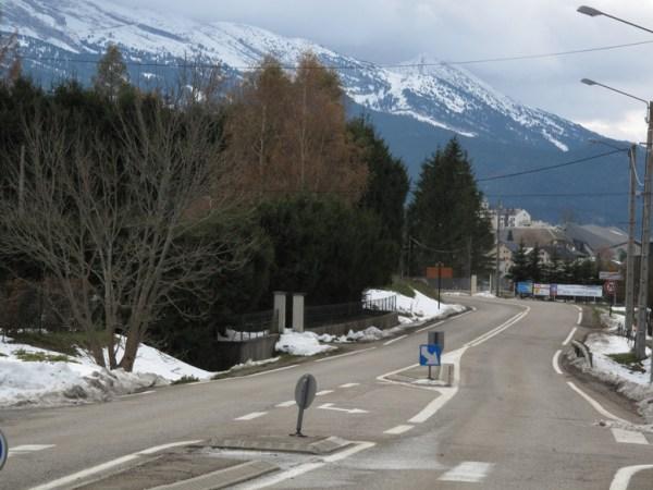 Ortsdurchfahrt im winterlichen Vercors mit Schnee am Straßenrand und auf den nebelverhangenen Bergen