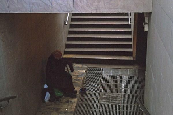 Einsame Bettlerin in einer Unterführung in Moskau, sich vor der winterlichen Kälte schützend