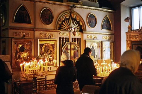Inneres einer orthodoxen Kirche in Moskau mit Gläubigen und brennenden Kerzen vor einer Ikonostase, gesehen bei einer vorweihnachtlichen Erkundungstour in Moskau