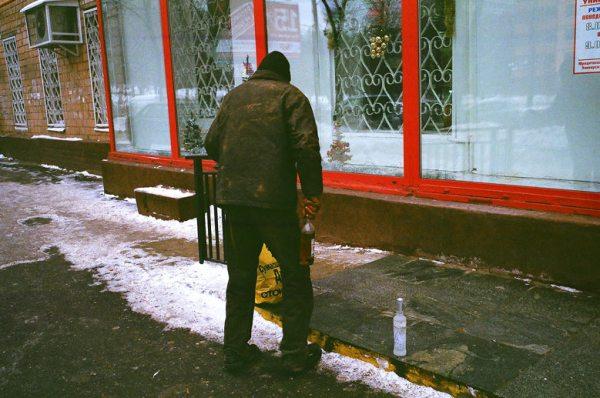 Vorweihnachtliche Erkundungstour in Moskau: Betrunkener Mann im Moskauer Winter mit einer Schnapsflasche in der Hand vor einem Schaufenster