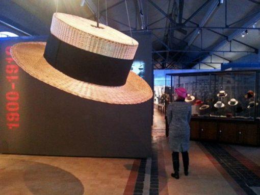 Bild von einem Riesenhut in einer Hutfabrik und einer eleganten Dame mit einem violetten Hut sowie verschiedenen Hutmodellen im Hintergrund