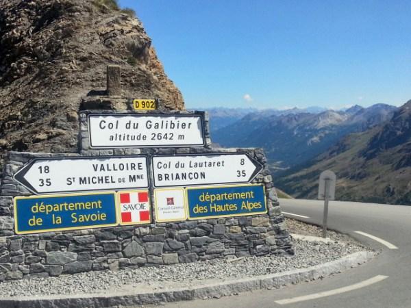 Schilder auf der Passhöhe des Col du Galibier mit Angabe der Höhe (2.642 m), den nächstgelegenen Orten und der beiden Départements, auf deren Grenze die Passhöhe liegt, hinterlassen große Lust auf Alpenpässe in Savoyen