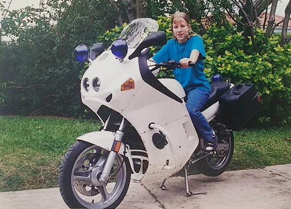Blondes Mädchen auf einem weißen Polizeimotorrad