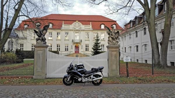 Schloss Wustrau Strassenseite mit einem dunkelgrauen Motorrad Yamaha FJR 1300 im Vordergrund