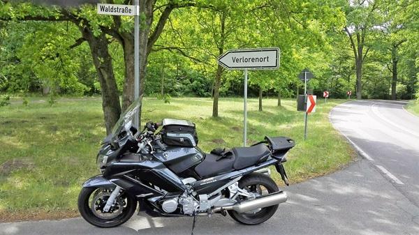Wegweiser nach Verlorenort mit einem dunkelgrauen Motorrad Yamaha FJR 1300 im Vordergrund