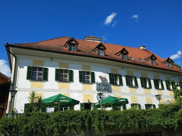 Bayerisches Gasthaus an der Donau mit einem Wirtsgarten und grünen Sonnenschirmen