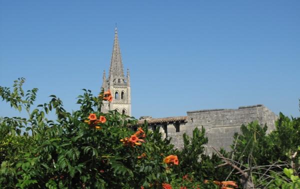 Kirche St-Emilion (Gironde) in Südwestfrankreich mit dem Kirchturm und einem orange blühenden Busch im Vordergrund
