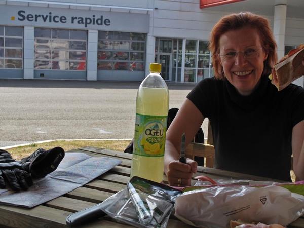 Rast in Dax im Département Landes bei einer Motorradtour Südwestfrankreich mit einer rothaarigen Motorradfahrerin und dem Schild Service Rapide im Hintergrund