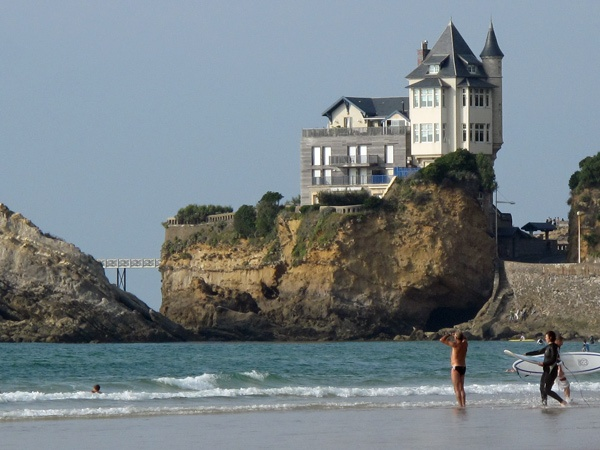 Strandszene im Seebad Biarritz mit Surfern im Vordergrund vor einem grossen Felsen mit einem darauf gebauten Holzhaus
