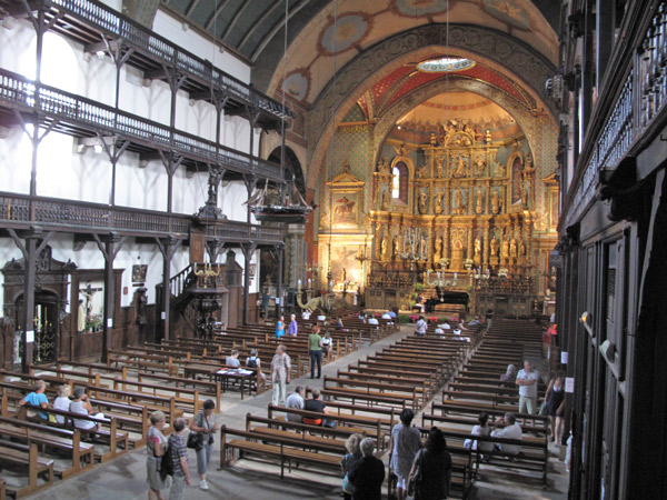Innenansicht der Kirche St-Jean-Baptiste in St-Jean-de-Luz (Nouvelle Aquitaine) mit einem reich geschnitzten, gold verzierten Altar, zweistöckigen Emporen und Kirchenbesuchern