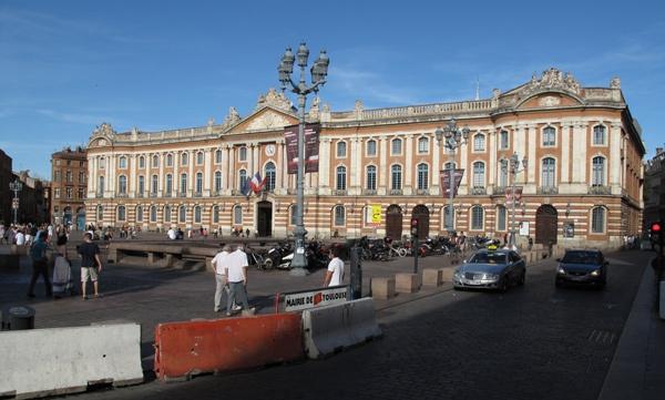 Rathaus und Capitol von Toulouse, mit einem weiten Vorplatz, einer gusseisernen Strassenlaterne, geparkten Motorrädern und Autos