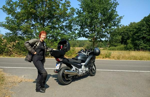 Motorradtour durch die Sächsische Schweiz mit einer rothaarigen Motorradfahrerin und einer dunkelgrauen Yamaha FJR 1300 am Strassenrand mit Wildobstbäumen im Hintergrund bei einer Motorradtour durch die Sächsische Schweiz