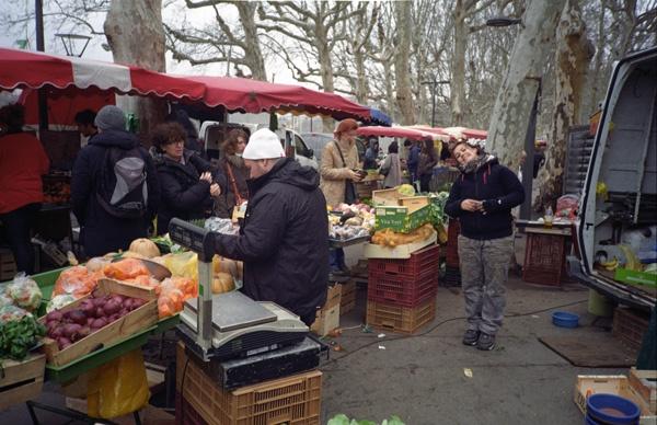 Marché St-Antoine in Lyon mit einem reichen Angebot von Obst, Gemüse und Käse auf den Marktständen, darum herum Kunden und Verkäufer im Gespräch. Hier gibt es auch die Zutaten für Maronensuppe mit Steinpilzen.