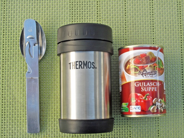 Dose Gulaschsuppe und Thermosbehälter mit einem Feldeßbesteck als Beispiel für Essen auf Rädern bei einer winterlichen Motorradtour