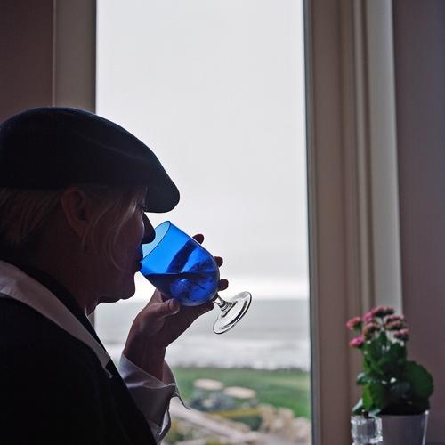 Person mit einem blauen Glas vor einem Fenster mit Blick auf den Pazifik