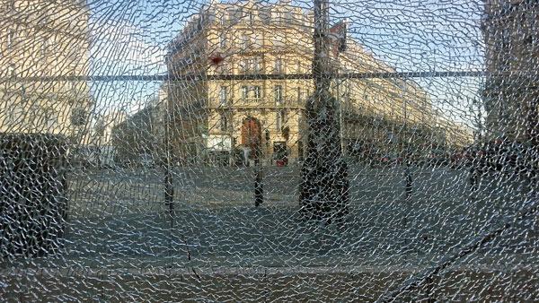 Zerbrochene Glasscheibe in Marseille mit Durchblick auf die Strasse und die dahinterliegenden Gebäude