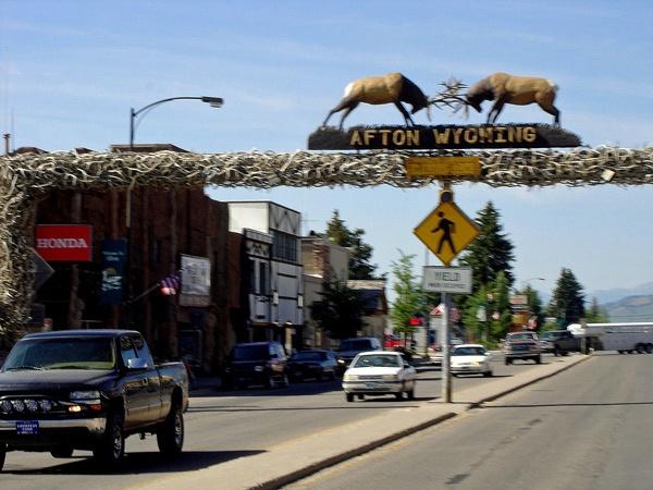 Hauptstrasse von Afton, WY mit vorbeifahrenden Autos und der Skulptur von zwei verkämpften Hirschen über der Straße