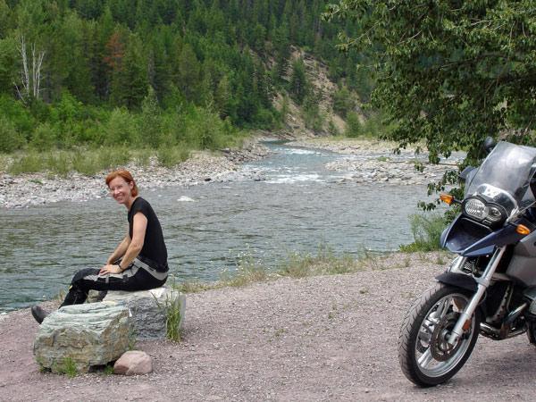 Rothaarige Motorradfahrerin am Flathead River in Montana mit einer BMW R 1200 GS
