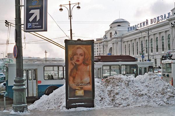 Werbeplakat mit barbusiger Frau vor einem Schneehaufen am Kiewer Bahnhof in Moskau mit eine Oberleitungsbus im Hintergrund