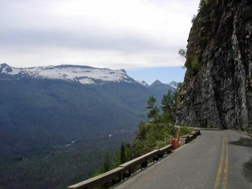 Bild von der Strasse auf dem Logan Pass in Montana mit steiler Felswand rechts und Blick ins Tal links