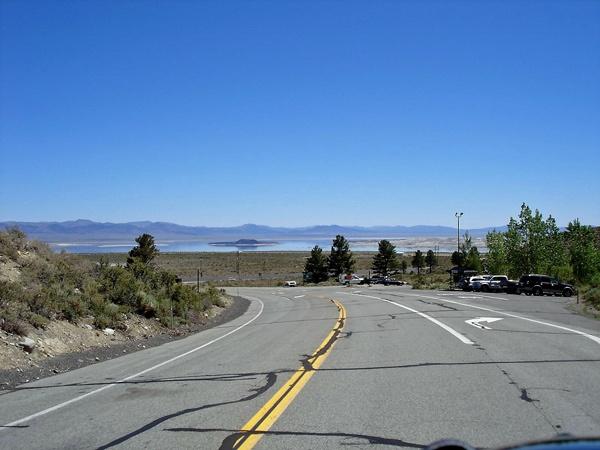Strasse zum Mono Lake mit dem See im Mittelgrund und der Sierra Nevada im Hintergrund, gesehen bei einer Motorradtour durch die Rocky Mountains