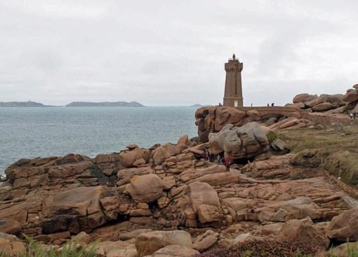Bild der Atlantikküste bei Perros Guirec in der Bretagne mit roten Felsen und einem roten Leuchtturm