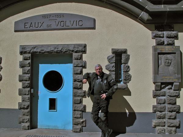 Brunnenhaus von Volvic in Frankreich mit einem Motorradfahrer und einer blau gestrichenen Türe