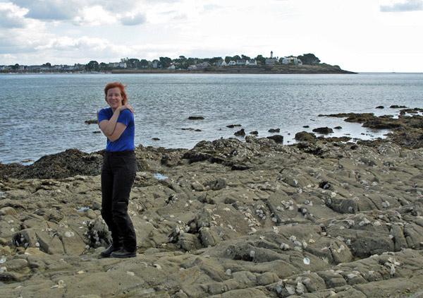 Strand von Locmariaquer an der bretonischen Atlantikküste mit einer fröstelnden rothaarigen Motorradfahrerin im blauen Hemd