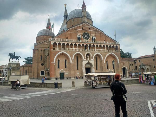 Rothaarige Motorradfahrerin vor der Basilica Sant Antonio in Padua bei einer Motorradtour nach Süditalien