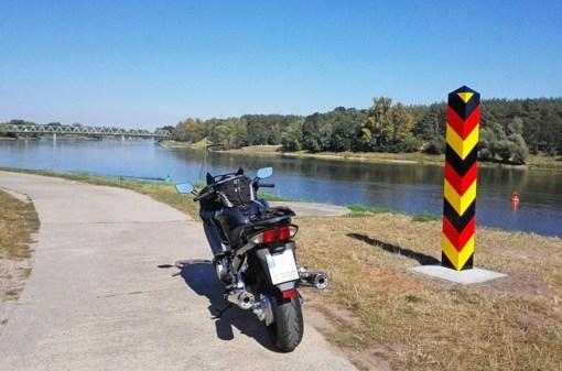 Motorrad auf einem Oderdeich mit deutschem Grenzpfahl bei einer Motorradtour durch das Oderbruch