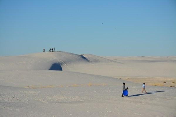 Gente caminando por la arena. Algunos llevan una especie de trineo en el que se delizan por las dunas.