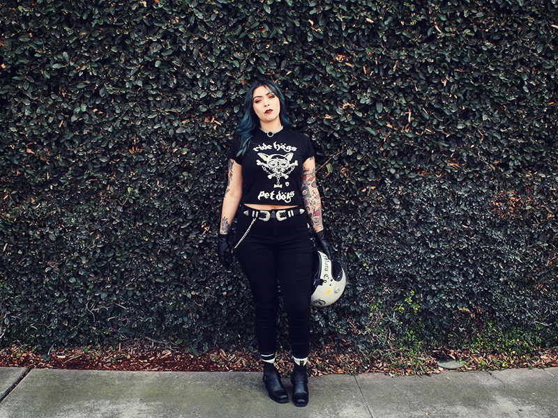 alternative woman with tattos and green hair standing in front of a bush wearing all black and a shel wolf Ride Hogs Pet dogs tshirt, holding a retro style biltwell helmet