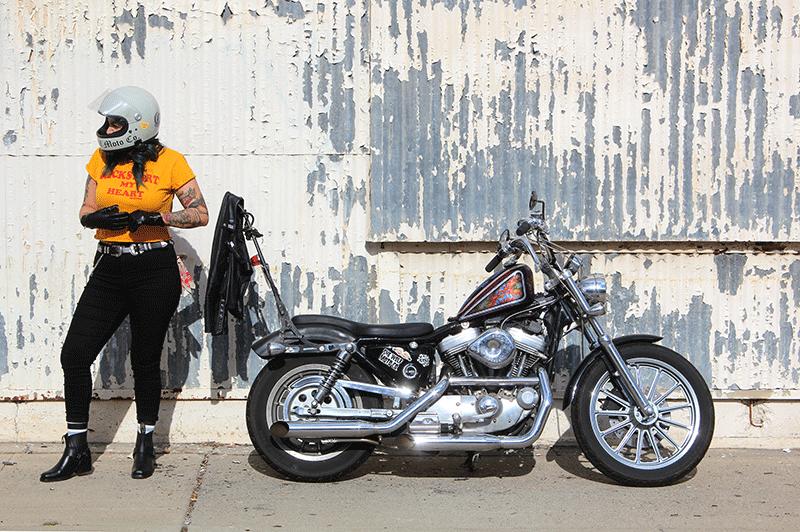 alternative tattooed woman with green hair wearing retro biltwell helmet beside a custom harley sportster 883