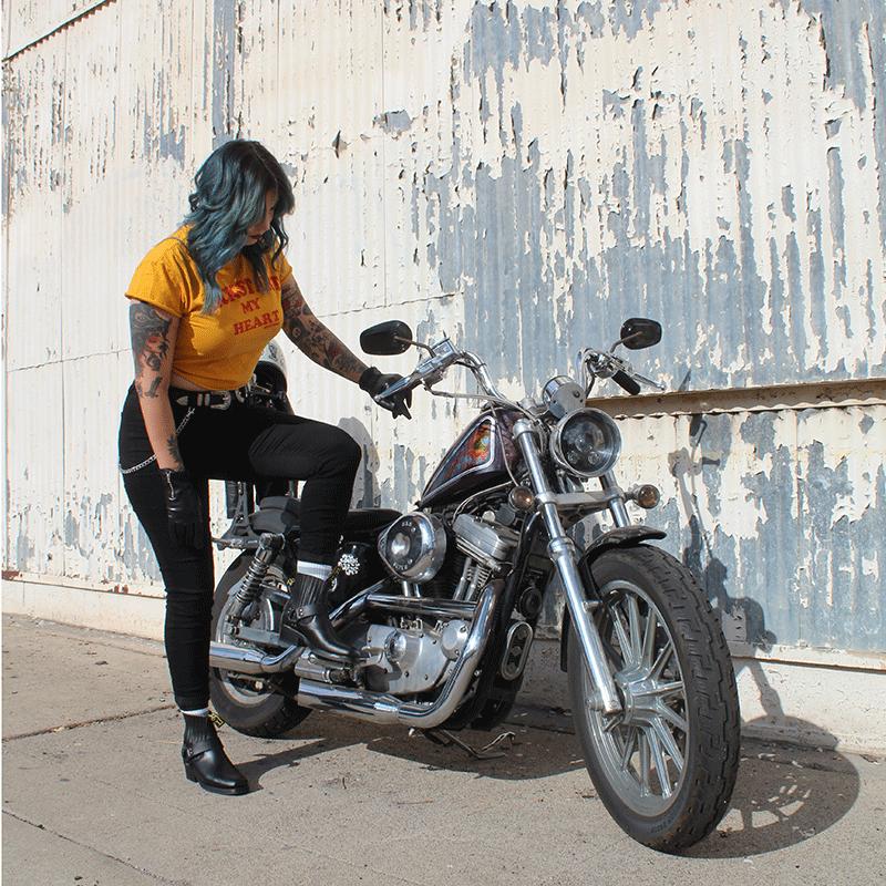 alternative woman with green hair kick starting custom harley sportster 883