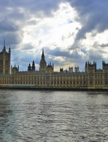 Houses of Parliament on far side of river, showing Gothic spires against dramatic sky
