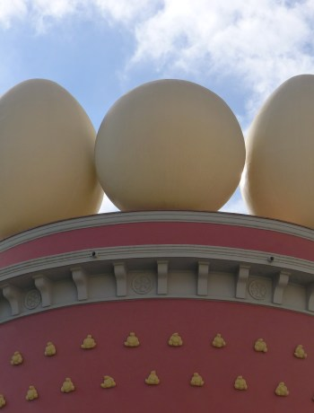 Three giant eggs on top of the roof of a red tower with gold spots against the blue sky