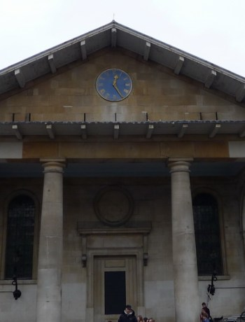 Front of a Palladian style church in light stone with a blue clock dial at the top