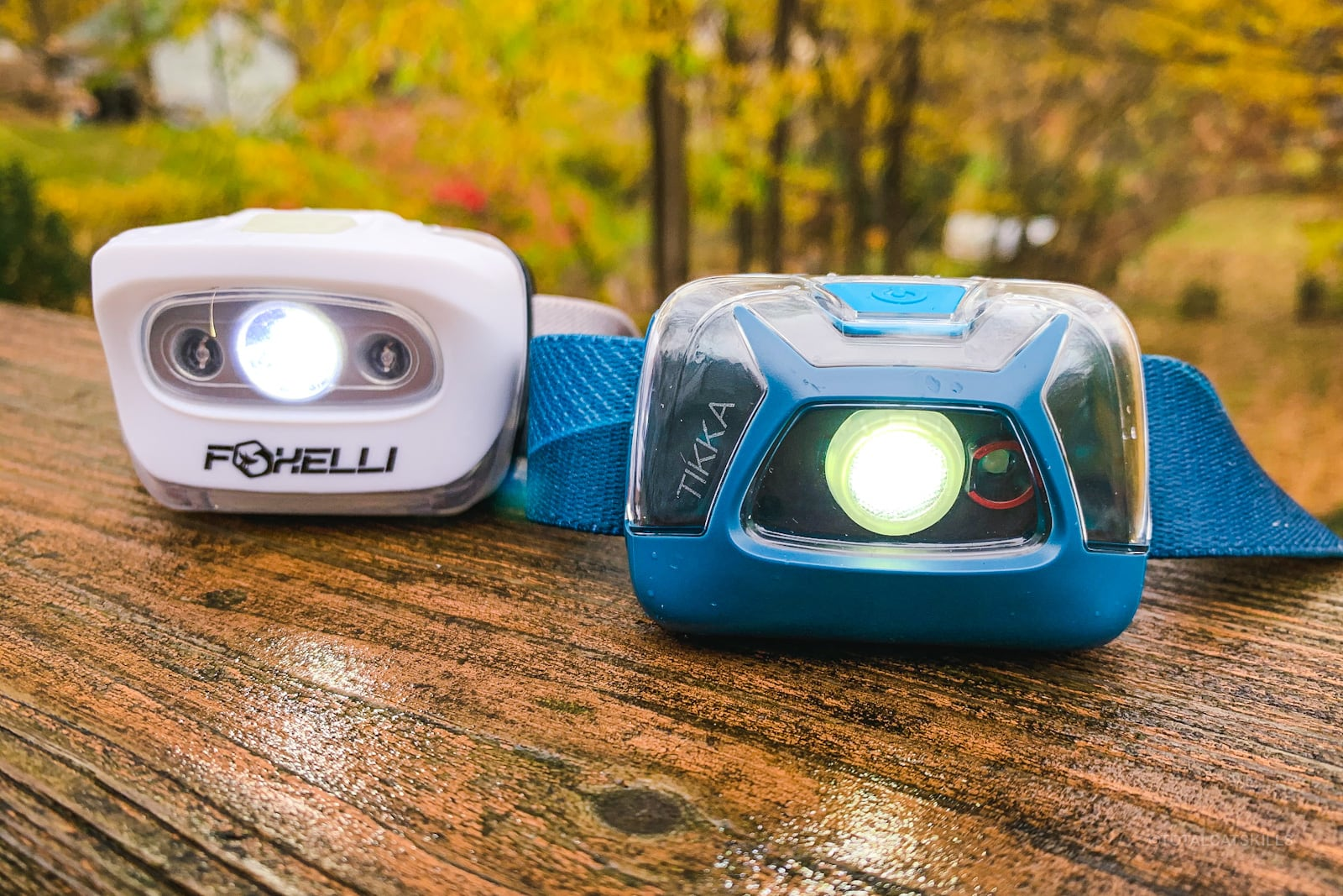 white and blue headlamps sitting on wet wood in woods