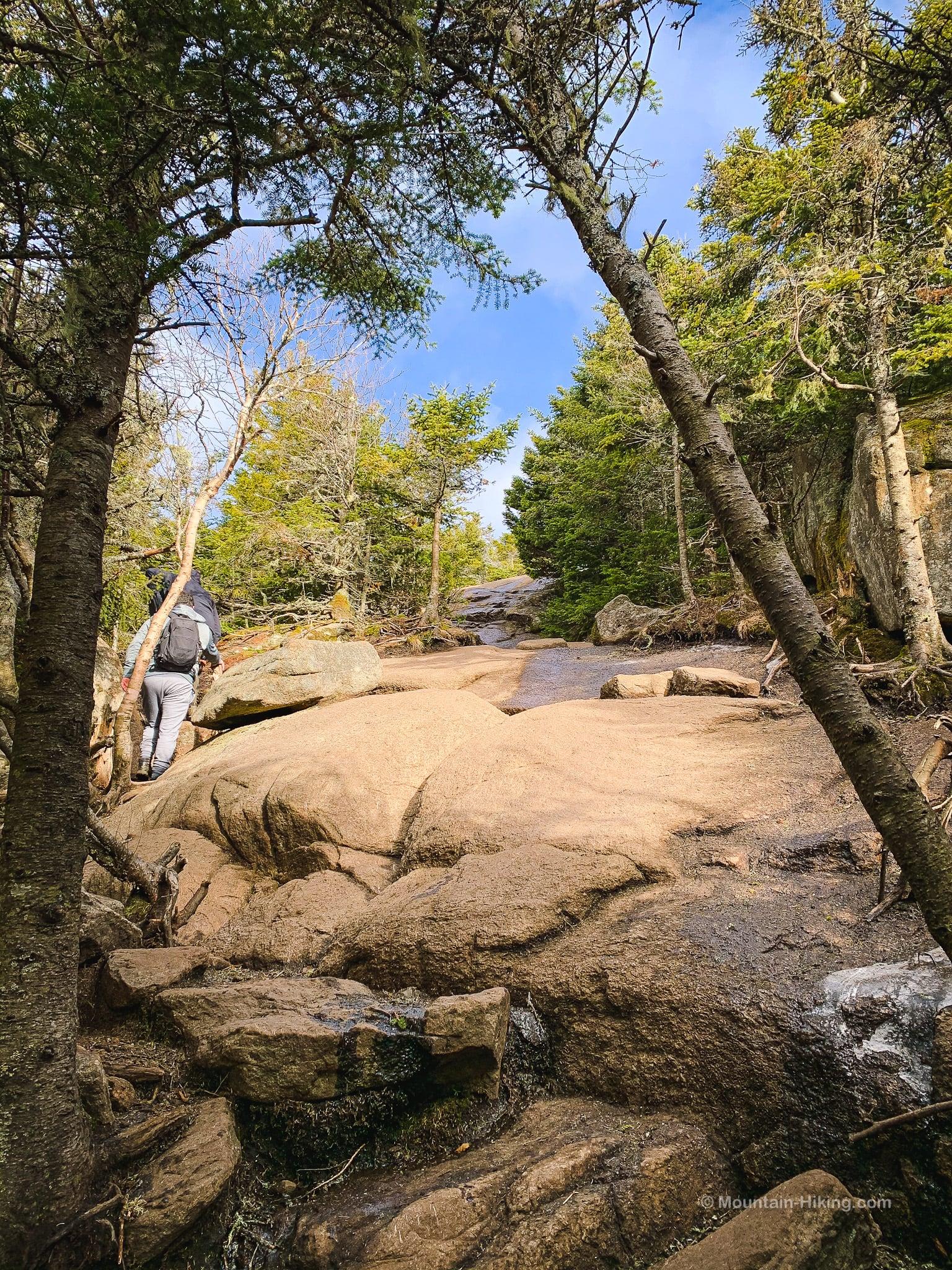 hiker traversing exposed rock slabs