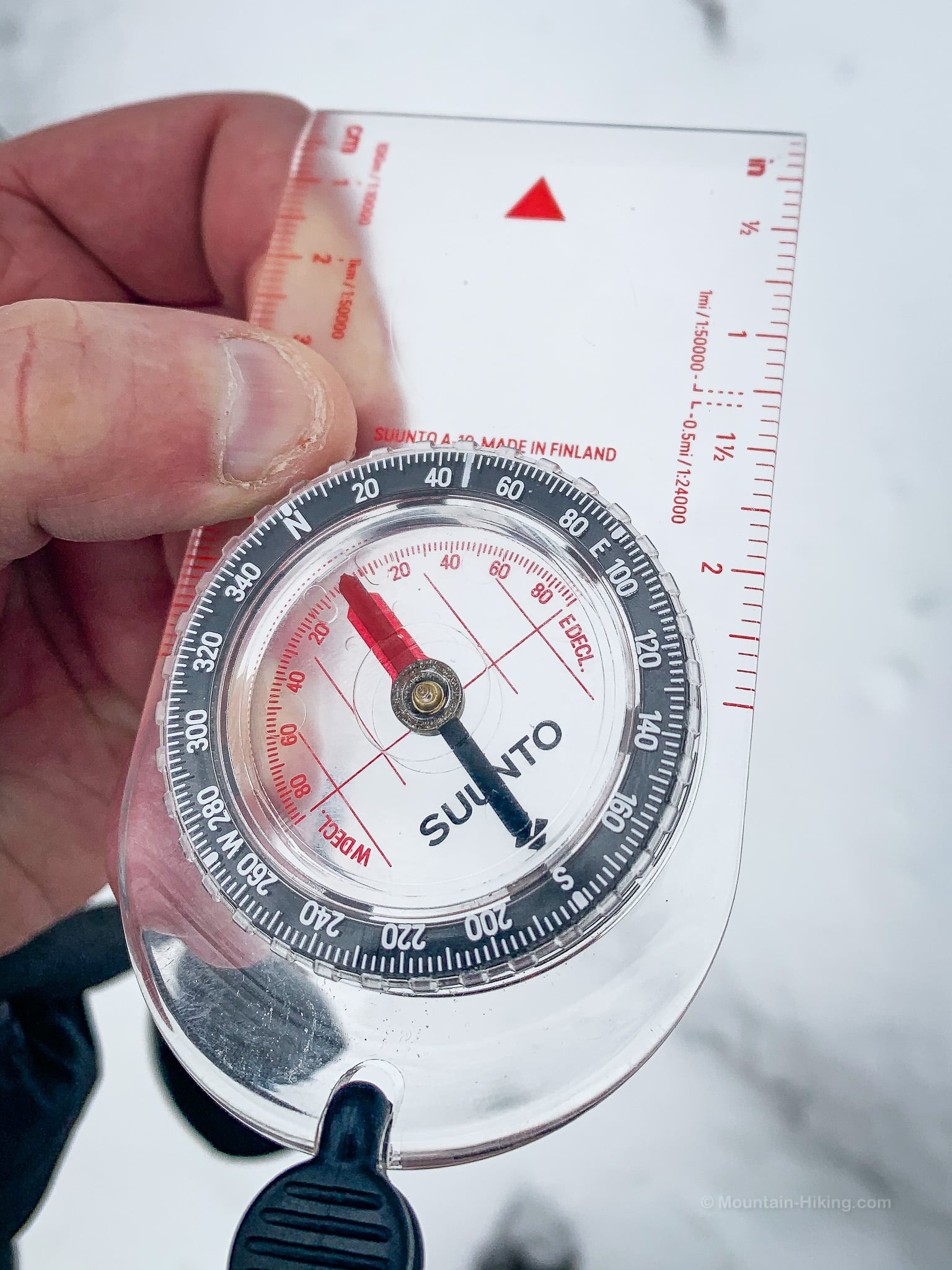 hand holding clear plastic compass over snow