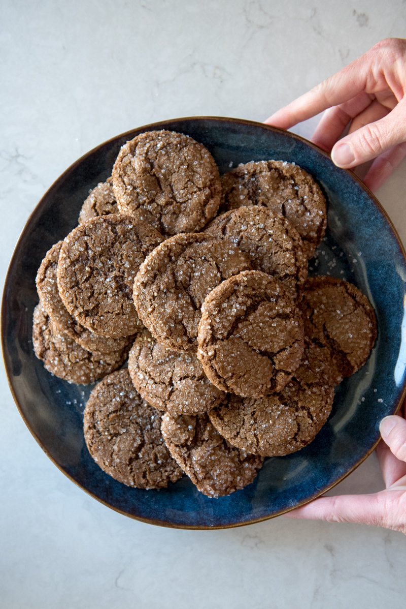 A large, blue dinner sized plate filled with sugar coated ginger cookies. Two hands holding the plate in the picture frame. www.mountainmamacooks.com