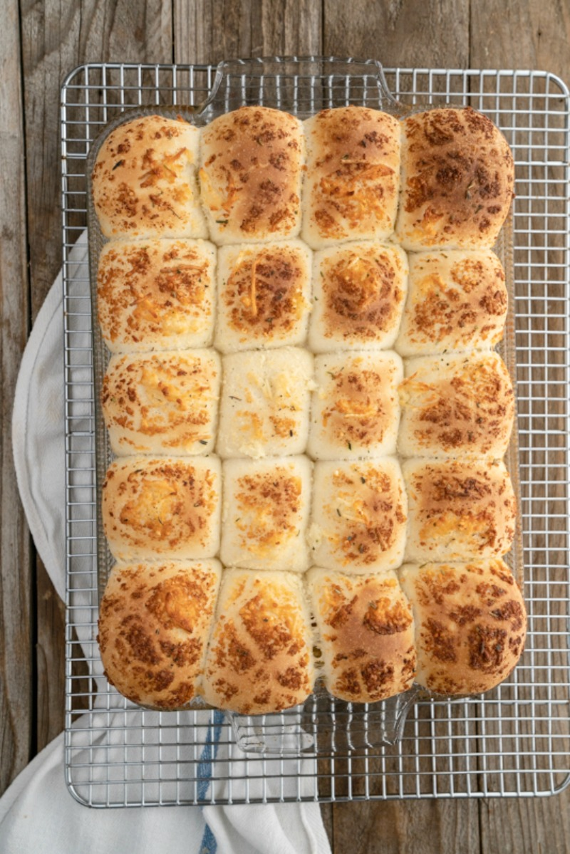 A wooden surface with a tray of warm-from-the-oven Parmesan dinner rolls. www.mountainmamacooks.com