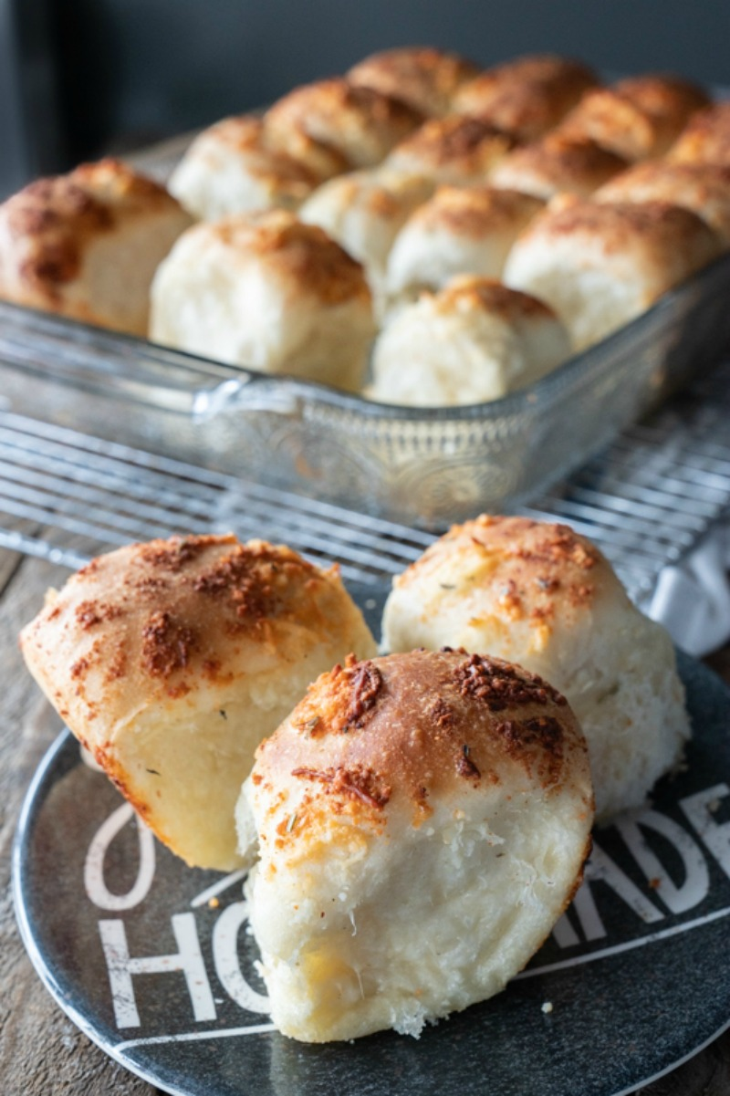 Three garlic parmesan rolls on a plate in front of a pan of warm rolls right from the oven. The tops are golden brown from the garlic butter and parmesan cheese. They are just begging for a smear of butter! www.mountainmamacooks.com